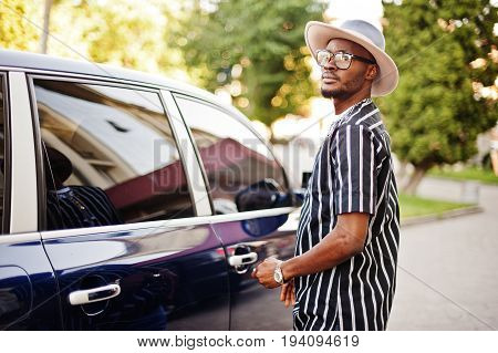 African American Man Stylishly Dressed Opening The Door Of His Cool Car.