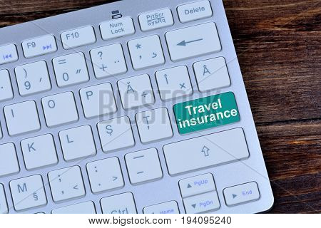Travel insurance on computer keyboard button closeup