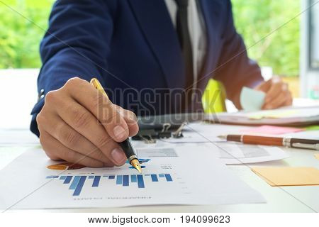 Businessmen are analyzing graph data and taking notes on a flip chart,Male office workers are analyzing data from charts and taking notes on a flip chart.