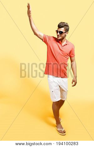 Fashionable man with stubble wearing sunglasses saluting while walking against yellow background.