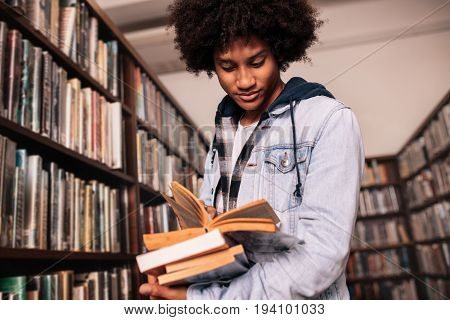 African male college student standing in library with lots of books. University student looking for study references.
