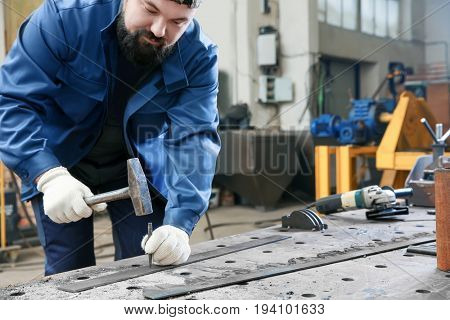 Man using hammer for metalworking in shop