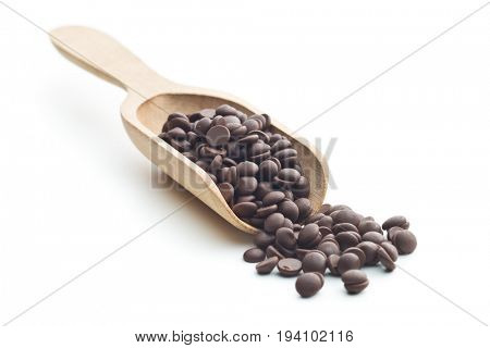 Tasty chocolate morsels in wooden scoop isolated on white background.