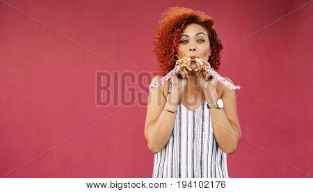 Young Woman In Playful Mood Blowing Party Whistles.