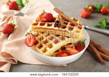 Delicious cinnamon waffles with strawberry on table