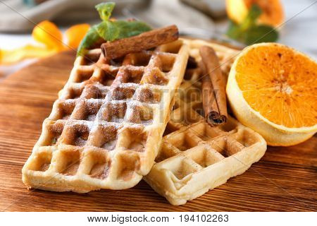 Delicious cinnamon waffles with orange, closeup