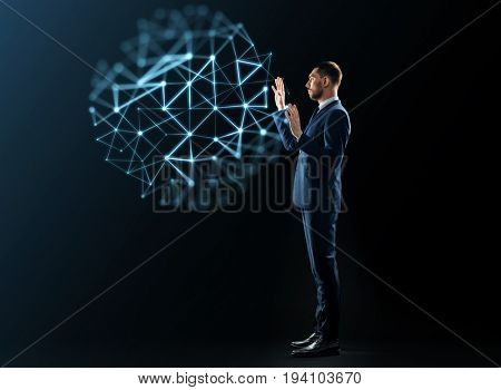 business, network, people and technology concept - businessman in suit working with virtual low poly projection over black background
