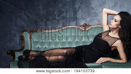 Beautiful and young woman posing in black dress on cyan sofa. Vintage interior and retro background.