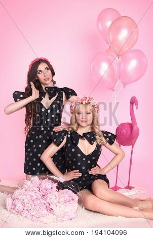 beautiful girls with doll make-up on pink background