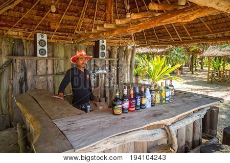 KOH KHO KHAO, THAILAND - NOVEMBER 10, 2012: Thai man standing on the beach bar of Koh Kho Khao island in Thailand. Koh Kho Khao is a tropical island at Andaman sea in Phang Nga province of Thailand.