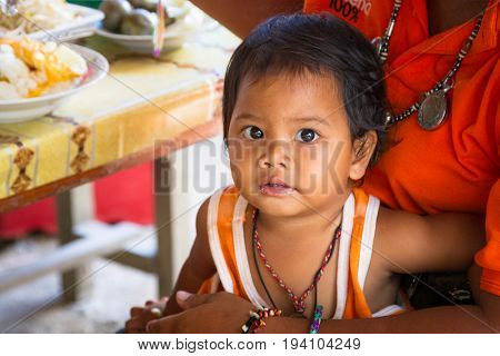 KHAO LAK, THAILAND - NOVEMBER 5, 2012: Cute toddler portrait sitting on mother knees in Khao Lak, Thailand. Many people in Thailand working with little babies with them.