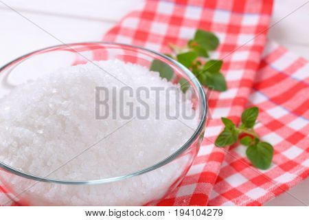 bowl of coarse grained sea salt on checkered dishtowel - close up