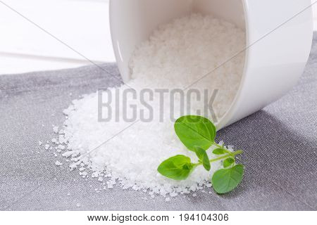 bowl of coarse grained sea salt spilt out on grey place mat - close up