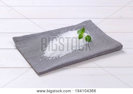 pile of coarse grained sea salt on grey place mat