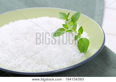 plate of coarse grained sea salt on grey place mat - close up