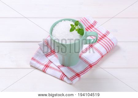 cup of coarse grained sea salt on checkered dishtowel