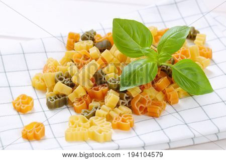 pile of raw colored pasta on checkered dishtowel - close up