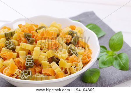 bowl of raw colored pasta on grey place mat - close up
