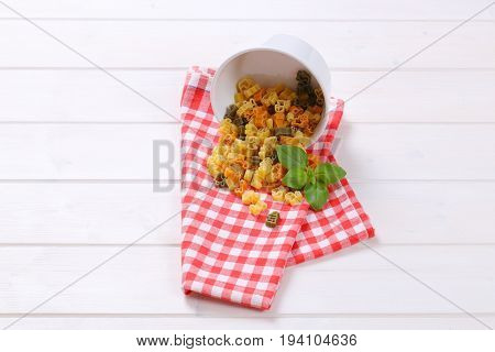 bowl of raw colored pasta spilt out on checkered dishtowel