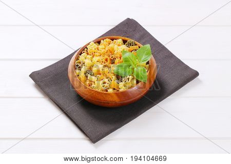 bowl of raw colored pasta on dark grey place mat