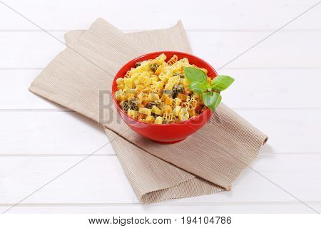bowl of raw colored pasta on beige place mat
