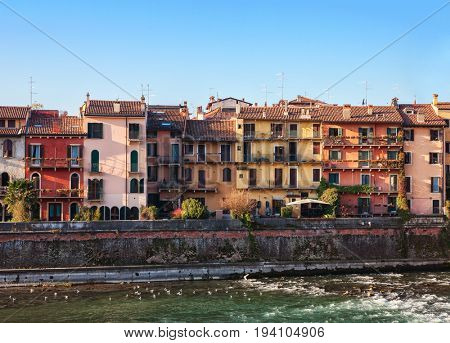 The picturesque views of the houses facades near the Adige river bank, Verona, Italy.