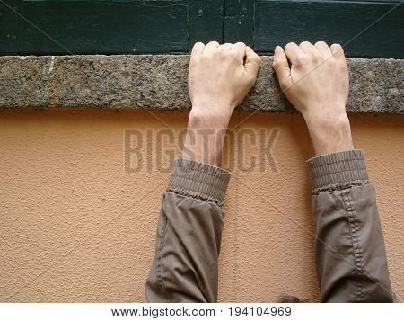 boy hanging on his hands at a window sill
