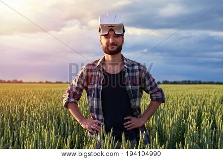 Young bearded man standing on field of weed wearing 3D glasses on head, looking in camera, mid shot