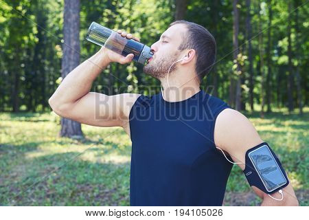 Mid shot of an athlete wearing sport cloth and phone in case on his hand. Listening to music, allaying thirst