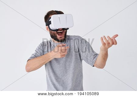 Close-up shot of bearded man playing a virtual reality simulation with glasses making gestures with hands as if using a weapon