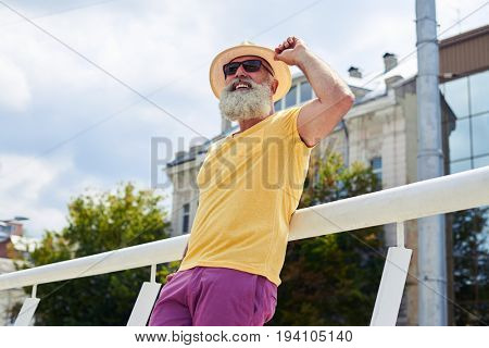 Low angle of urban bearded man with his hand holding brim of straw
