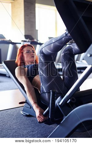 Side view of slim middle aged woman doing leg exercises with machine in gym
