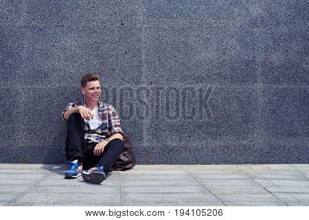 Mid shot of good-looking man leaning on wall while listening to the music. Handsome man resting outdoors