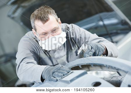Repair man worker sanding automobile car body in garage