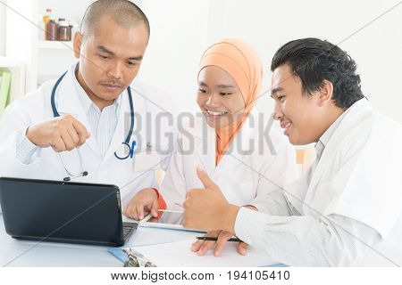 Group of doctors discuss at meeting in hospital office and showing thumb up. Southeast Asian Muslim medical people.