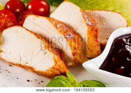 Roast chicken breast and vegetables on white background