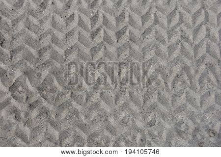close up view of zigzag tire track pattern in sand