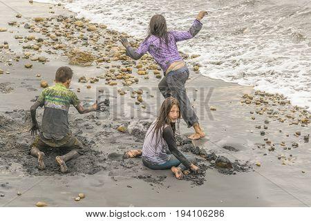SALINAS, ECUADOR, JULY - 2016 - High angle shot of three teens playing at shore of beach in Salinas Ecuador