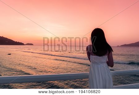 Pretty woman enjoy view of beautiful colorful sunset sky on tropical beach in twilight time at Patong beach in Phuket province The most famous tourist attraction in Phuket province Thailand.
