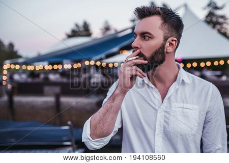 Brutal handsome man is smoking sigarette outdoors.