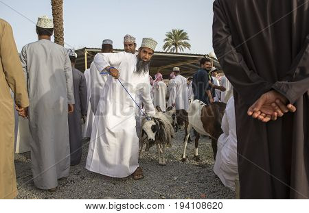 Nizwa Oman June 23rd 2017: omani man in traditional clothing at a habta market selling his goat