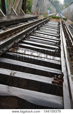 Closeup of tilted railway road on a bridge in a rainy day; perspective from below
