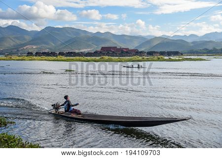 local man on the boat in Inle lake with beautiful mountain landscape located in the Nyaungshwe Township of Taunggyi Shan State Myanmar