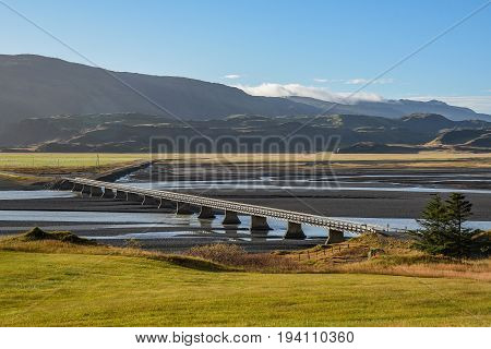 empty long road bridge cross over river beautiful mountain and field landscape in summer of Iceland famous destination for road trip travel