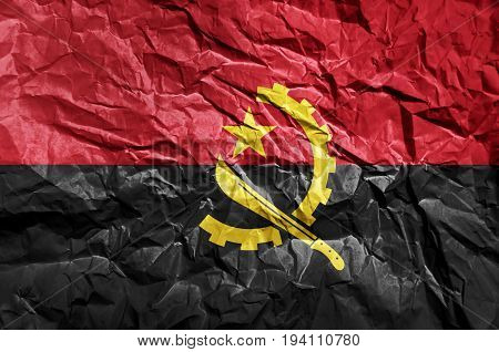 Angola flag painted on crumpled paper background