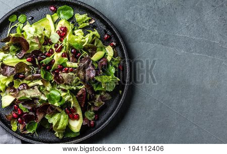Lettuce salad with pomegranate on black plate, slate background