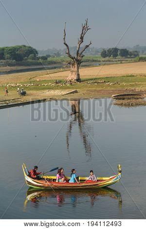 AMARAPURA MYANMAR - DECEMBER 24 2016 : People on traditional boat in Taungthaman Lake and iconic tree near U Bein Bridge tourist attraction of Amarapura Township Mandalay Myanmar (Burma).