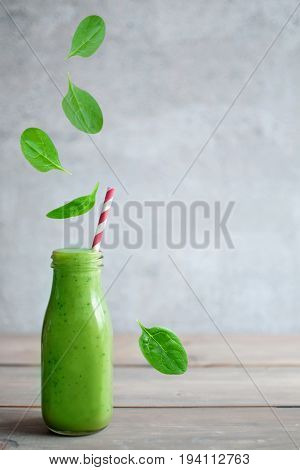 Fresh leafy greens falling into a smoothie bottle with space for text