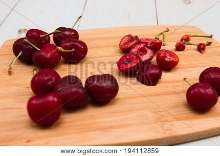 Cherries being prepared on a wooden board