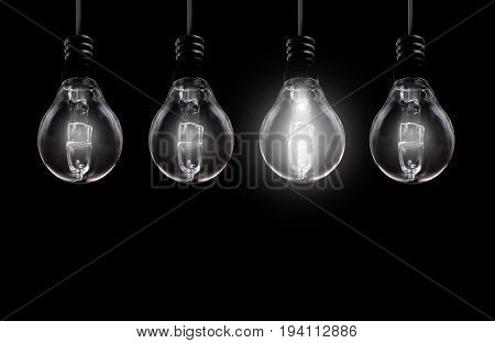 Brightly lit bulb on background with space in a row of unlit lamps